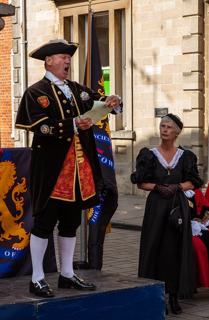 A town crier, wearing Georgian era regalia, spreads the news from a stand in the town square.